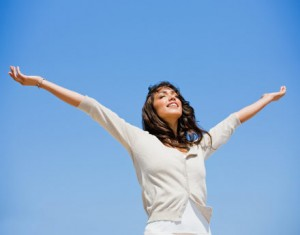 Pretty young woman with arms raised against blue sky